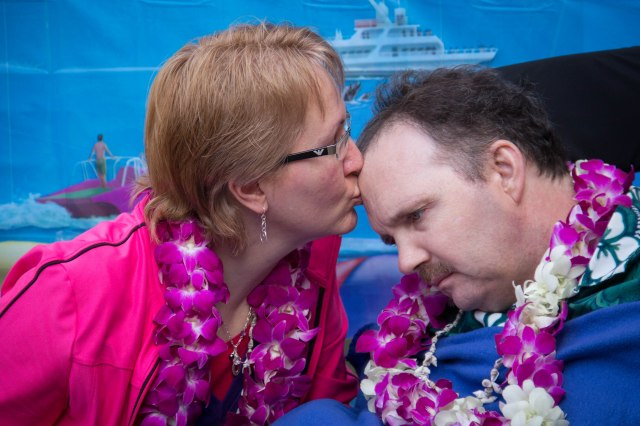 Debbie kisses her husband, Chris, who was diagnosed with younger onset Alzheimer's at 45.