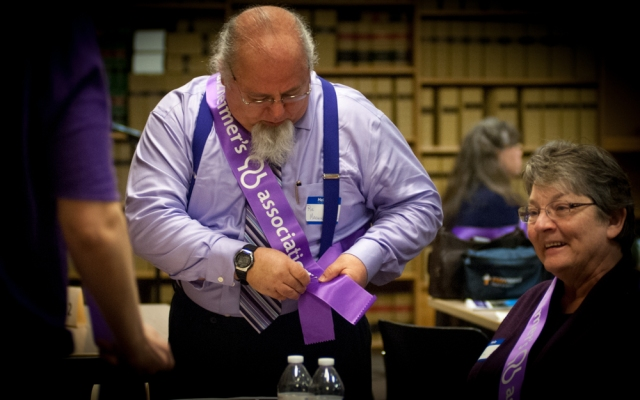 An advocate adjusts his sash before visiting Legislators.  105 people wore Alzheimer's Association sashes and spoke to legislators about the urgency of a several bills that will help those affected by Alzheimer's and other dementias.