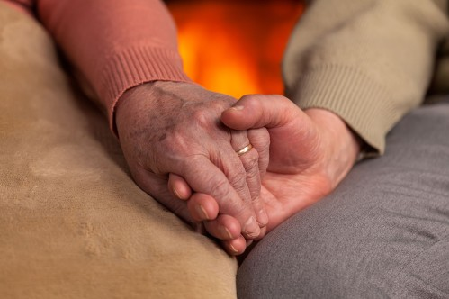 Senior old hands holding in front of fireplace